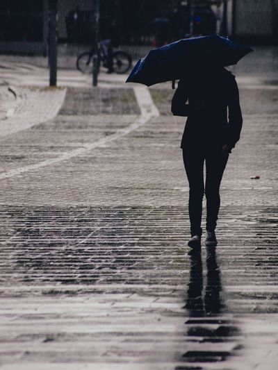 Full length of person carrying umbrella walking on wet cobbled street during rainy season