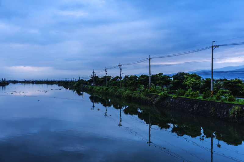 Power lines by water at dusk