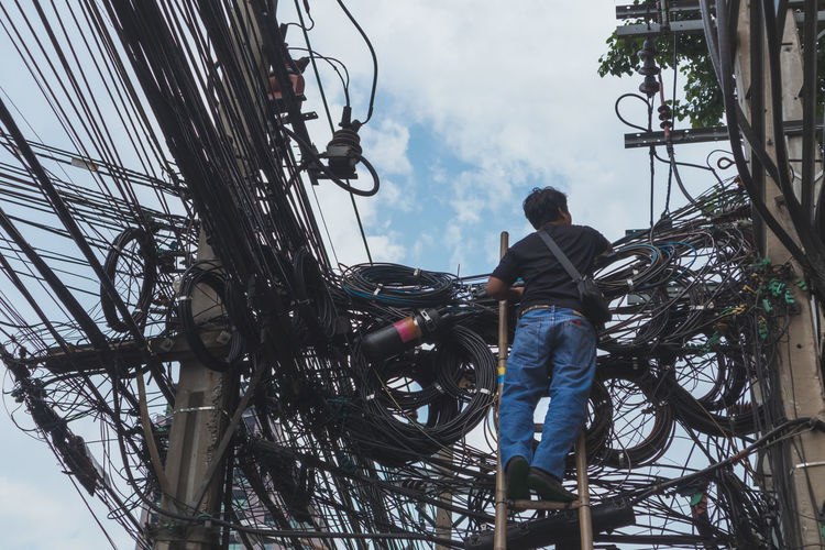 Low Angle View Of Man Working On Electricity Pylon Against Sky