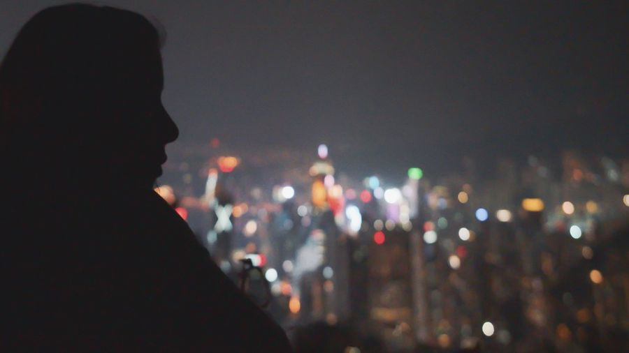 Silhouette woman against illuminated city at night