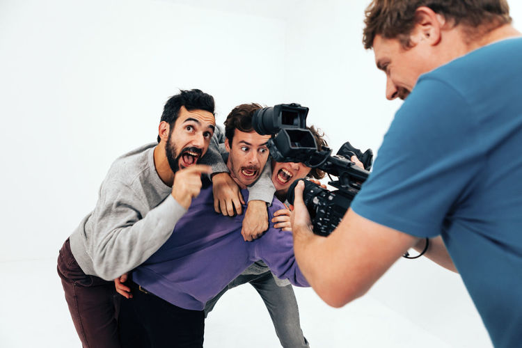Three people acting in front of the camera in a white studio background