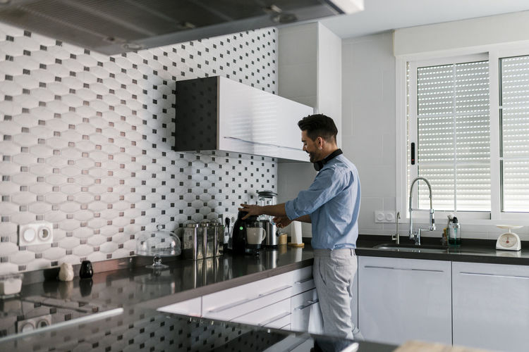 Side view of young man standing in kitchen