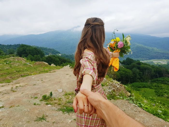 Man holding woman hand in nature