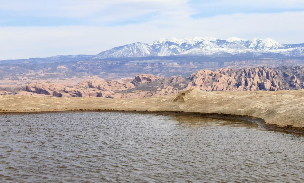 An ephemeral water hole atop Long Canyon outside Moab Utah. Sandstone fins and the La Sal Mts beyond. Beauty In Nature Day La Sal Mountains Landscape Mountain Nature No People Oasis Outdoors Scenics Sky Water Westworld