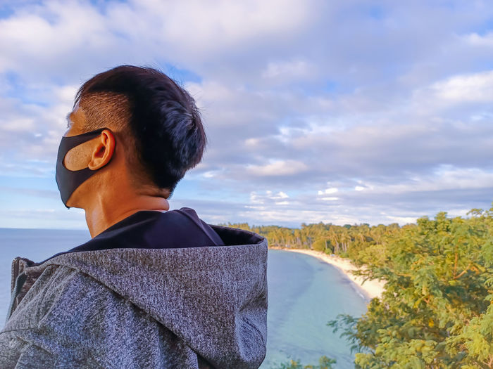 Rear view of man wearing mask looking at sea against sky