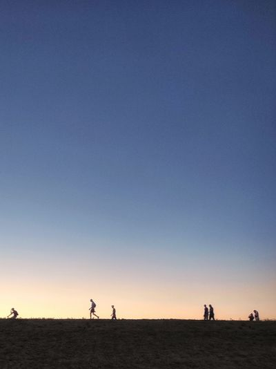 People on field against clear sky during sunset