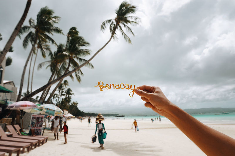 Cropped hand holding text at beach against cloudy sky