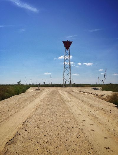Dirt road with tire tracks leading towards metal tower against sky