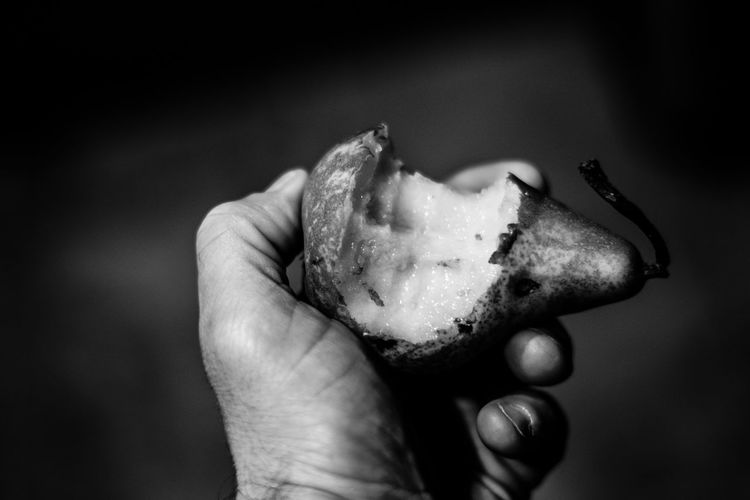 Cropped image of man holding pear