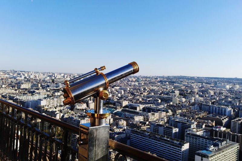 Hand-held telescope at observation point with city in background against clear sky
