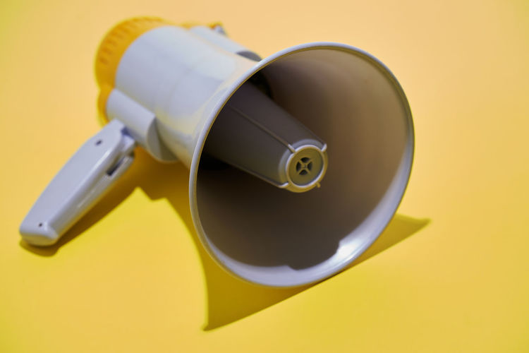 High angle view of camera on table against yellow background