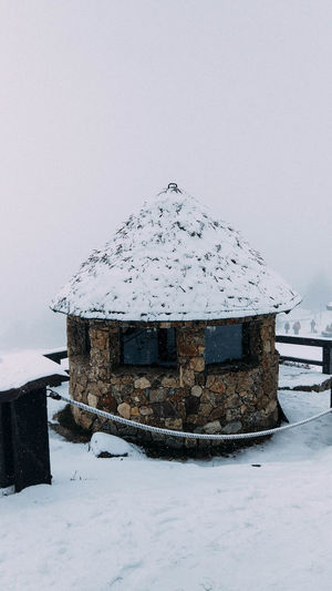 Built structure on snow covered mountain against sky