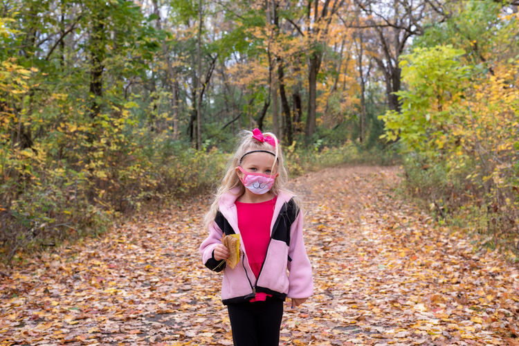 Portrait of girl standing against trees during autumn