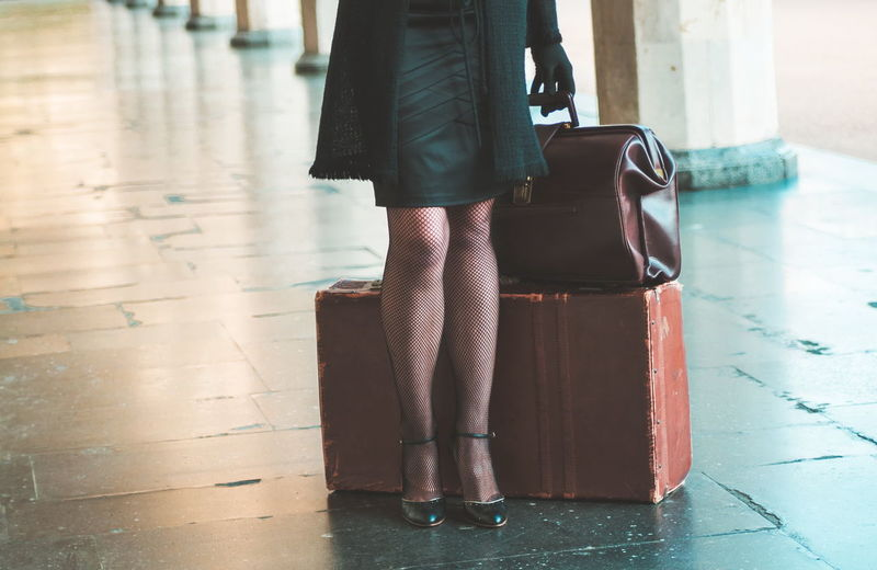 Low Section Of Woman With Luggage Standing On Corridor