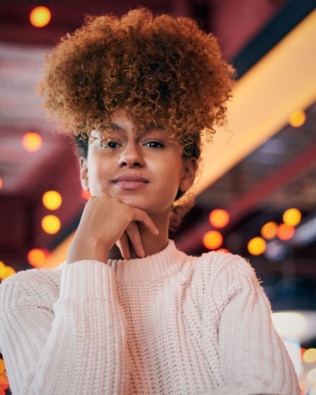 Portrait of young woman with curly hair at restaurant