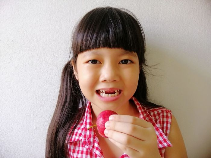 Asian girl holding an apple, she is eating an apple Daugther Love And Care Sweet Cute Girl Thai Food Fringe Hair Long Hair Fruit Apple Eating Lifestyle Holding Milk Teeth Broken Tooth Asian Girl Hungry Portrait Child Smiling Childhood Cheerful Girls Happiness Looking At Camera Headshot Studio Shot Brown Eyes Elementary Student SchoolGirl