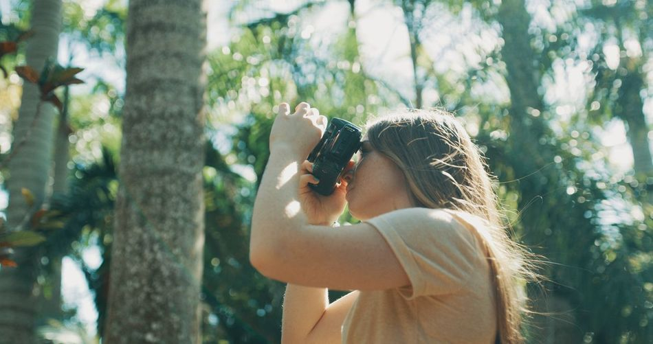 Midsection of woman holding camera while standing by tree