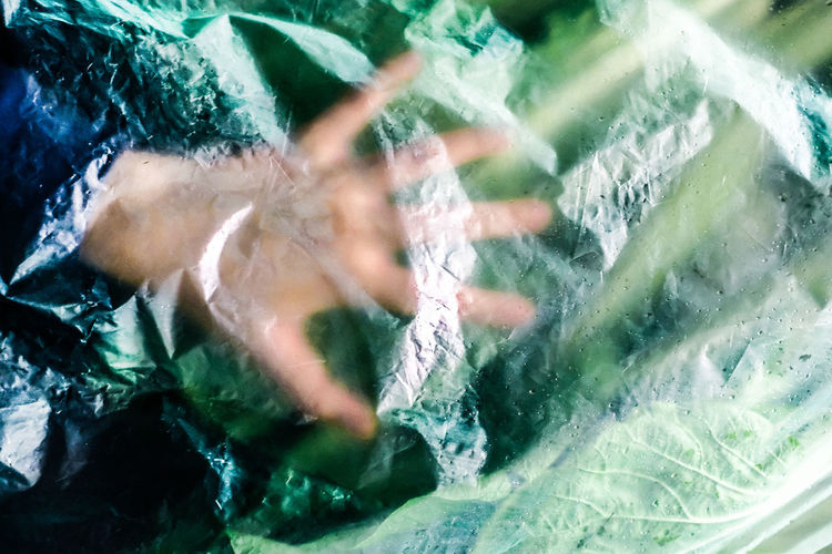 Cropped hand of person seen through plastic