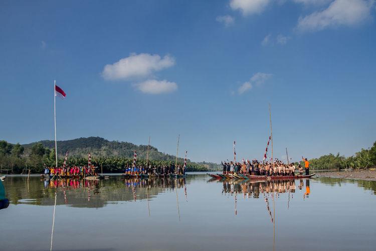 People sailing in lake against sky