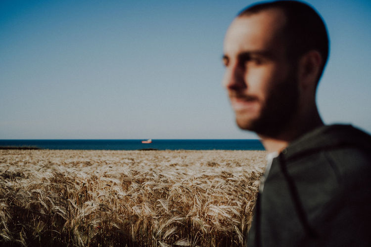 Portrait of young man looking at sea against sky