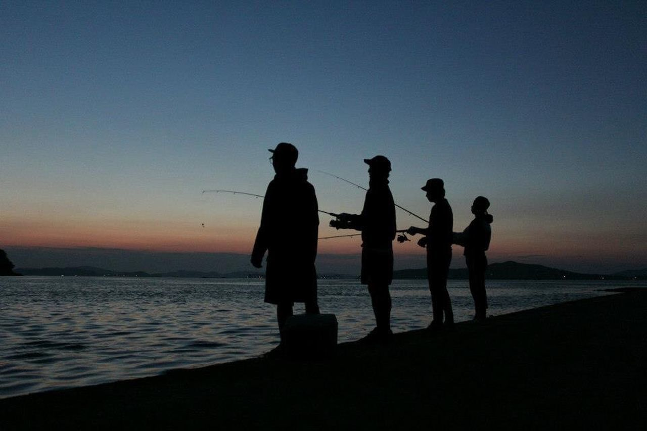 silhouette, sea, sunset, beach, water, standing, nature, men, real people, outdoors, scenics, horizon over water, sky, beauty in nature, togetherness, clear sky, lifestyles, full length, vacations, women, day, adult, people