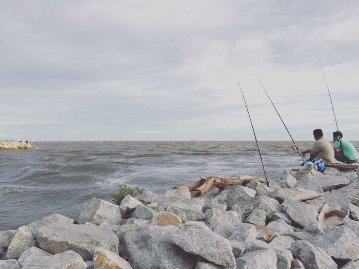 Sea Water Sky Cloud - Sky Rock - Object Nature Real People Horizon Over Water Day Outdoors Scenics Men Beauty In Nature Full Length Fishing Pole People
