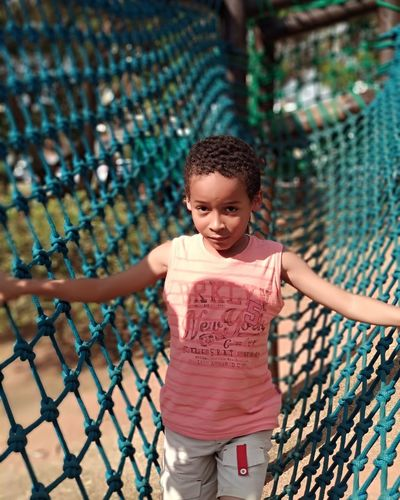 Portrait of boy climbing on net