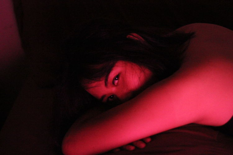 Close-Up Portrait Of Woman Leaning In Illuminated Room