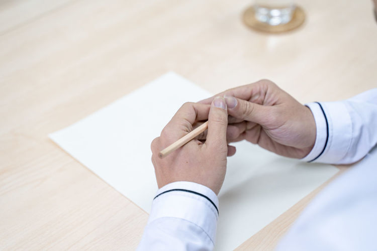 High angle view of man holding hands on table