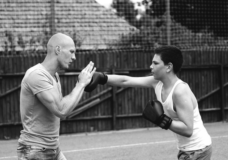 Side view of young male trainer teaching boxing to boy