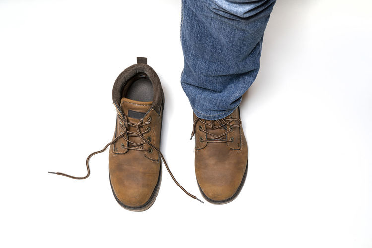 Low section of man wearing shoes standing against white background