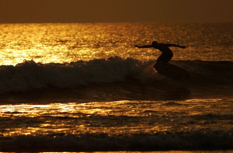 Man surfboarding on sea against sky during sunset