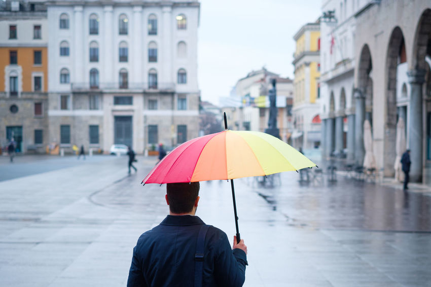 Rainy Days Architecture Building Exterior Built Structure City Day Focus On Foreground Men One Person Outdoors People Protection Rainy Real People Rear View Red Umbrella