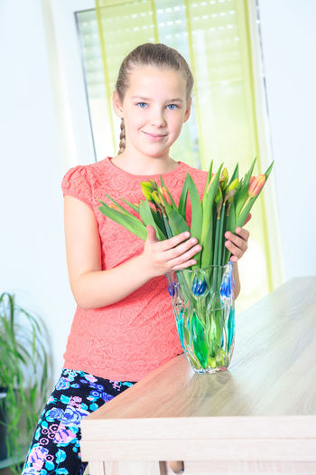 portrait of a teenage girl with flowers at home Beauty, Bouquet, Caucasian, Cute, Day, Face, Female, Floral, Flowers, Girl, Happiness, Home, House, Portrait, Pretty, Smile, Summer, Teen, White, Young, One Person Women Lifestyles Teenager Portrait Home Inside