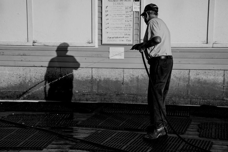 Fisherman's Wharf Working Architecture Blackandwhite Cap Casual Clothing City Day Fisherman Footpath Full Length Hat Leisure Activity Lifestyles Men Nature Outdoors People Real People Rear View Standing Sunlight Uniform Waiting Wall - Building Feature