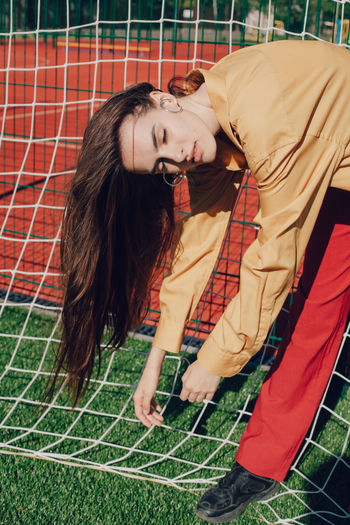 Young woman standing by soccer goal