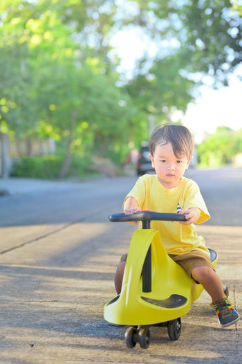 Portrait of cute boy riding motorcycle on road