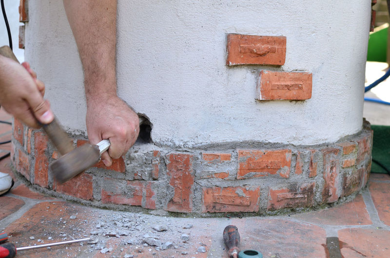 Close-up of man working on wall