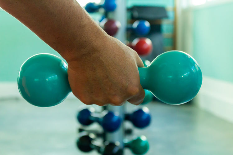 Ball Blue Body Part Close-up Finger Focus On Foreground Hand Holding Human Body Part Human Finger Human Hand Indoors  Leisure Activity Lifestyles Multi Colored One Person Real People Sport Weight Training  Weights