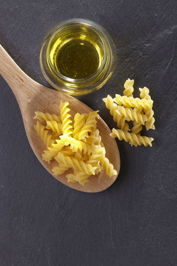Close-up of fusilli in wooden spoon with oil on slate