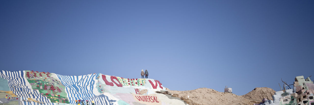 Man And Woman Standing On Cliff With Graffiti Against Clear Blue Sky