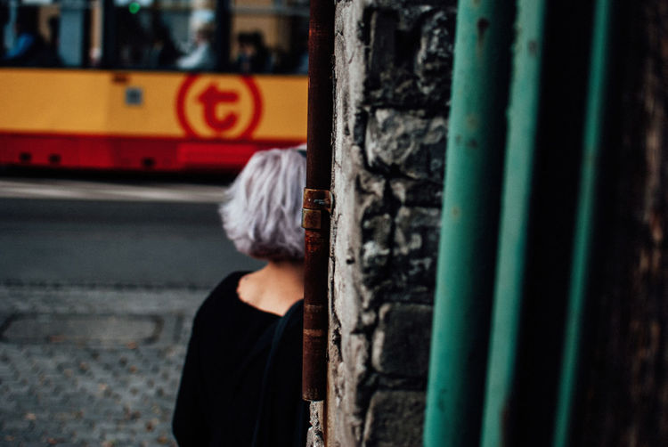 Rear view of woman standing by wall
