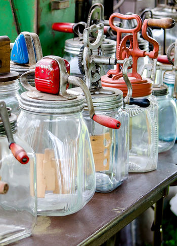 old time butter churn collection on display at a farm show. Antique Making Butter Old Fashioned Retro Butter Churns Collectable Items Collection Crank Power Glass Glass Jar Non Electric Old Houseware Paddle Tools