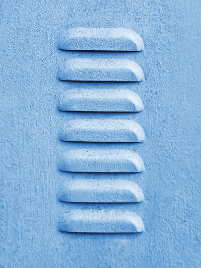 Close-up blue grainy painted sheet metal louvers pattern
