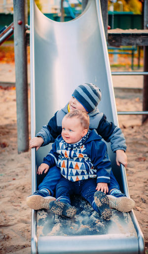 Cute sibling sitting on slide at playground