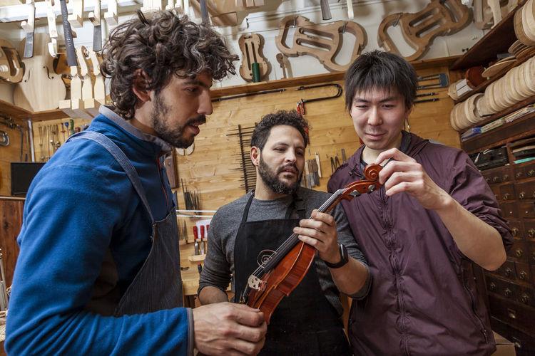 Male workers examining violin in workshop