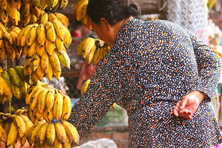 Rear view of woman standing by bananas at market