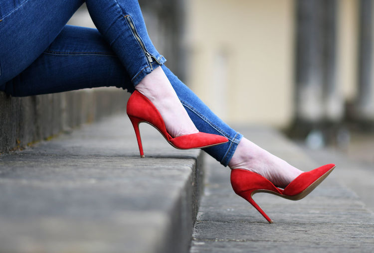Low section of woman wearing red shoes on steps