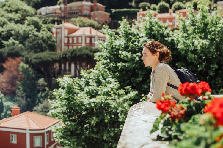 Woman standing by flowering tree against building