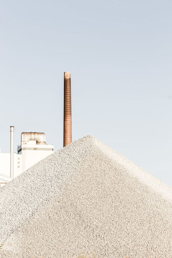 Chimney by sand against clear sky